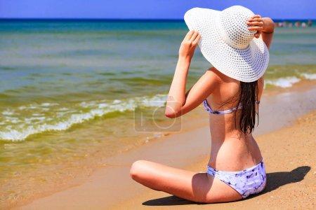 Foto de Hermosa mujer de sombrero de paja grande tomando el sol en una playa de arena. Concepto de vacaciones de verano - Imagen libre de derechos