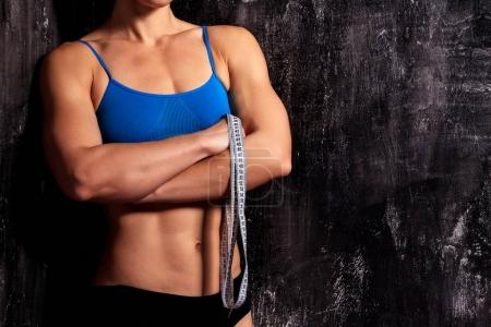 Photo for Strong fitness woman with a tape measure on dark background - Royalty Free Image