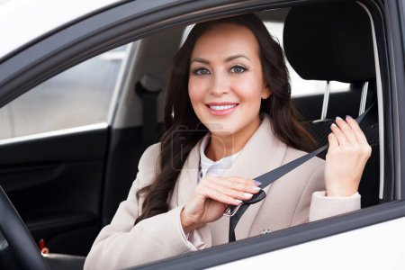 Photo for Portrait of young smiling, happy, pretty woman driver pulling on seatbelt inside white car. - Royalty Free Image