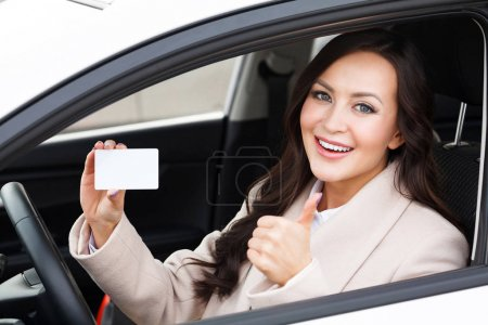 Photo for Beautiful young girl sitting in white car showing an empty white card and thumbs up hand sign - Royalty Free Image