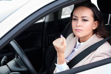Boorishness on the road. Young woman is showing her fist to someone
