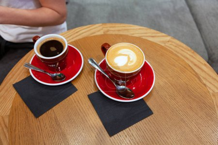 Photo for Two cups of coffee with latte art on wooden table - Royalty Free Image