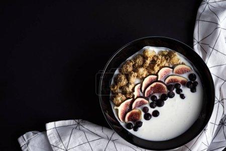 Photo pour Bol avec des figues fraîches et des baies sur le fond, vue sur le dessus, concept de petit déjeuner sain - image libre de droit