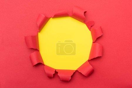 Photo pour Papier rouge avec trou déchiré de couleur jaune sur fond moyen, couche plane - image libre de droit