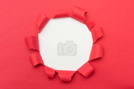 Photo pour Papier rouge avec trou déchiré de couleur blanche au milieu de l'arrière-plan. - image libre de droit