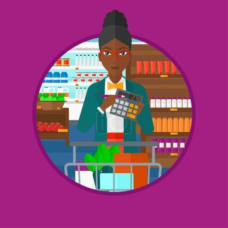 Illustration pour Une femme afro-américaine avec calculatrice et chariot de supermarché plein de produits. Femme vérifiant les prix avec calculatrice. Illustration vectorielle du dessin plat dans le cercle isolé sur fond . - image libre de droit