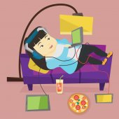 Asian fat woman relaxing on a sofa with many gadgets Woman lying on a sofa surrounded by gadgets and fast food Plump woman using many gadgets at home Vector flat design illustration Square layout