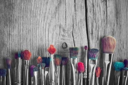 Photo pour Rangée de pinceaux d'artiste avec soies colorées en gros plan sur un vieux fond en bois, rétro noir et blanc stylisé . - image libre de droit