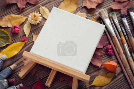 Photo for Canvas on easel, paint tubes, brushes for painting and autumn leaves on old wooden desk. Top view. Flat lay. Retro toned. - Royalty Free Image