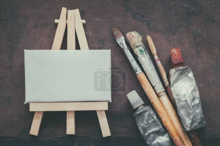 Photo for Artist paintbrushes, paint tubes and small easel with canvas closeup. Top view. - Royalty Free Image
