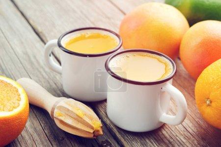 Photo pour Deux tasses à jus d'orange, presse-fruits en bois et agrumes . - image libre de droit