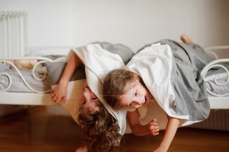 Children, boy and girl indulge on the bed in the bedroom.