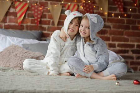 Two children in pajamas sitting on the bed waiting for Christmas gifts.