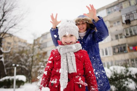 Mother with daughter cheerfully spend time in winter day.