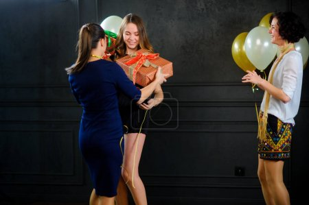 The girl receives congratulations and gifts from girlfriends.