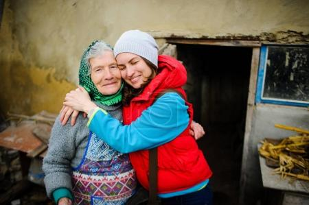 Photo for The young woman embraces the old woman. Love and tenderness of the granddaughter and grandmother. Rural farmstead. - Royalty Free Image