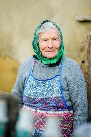 Photo for Old peasant woman. Calm, wise sight. gray hair from under a scarf. Wrinkled face. - Royalty Free Image