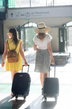 Photo pour Deux jeunes touristes à la gare. Dans les mains des jeunes filles valises, billets, passeports. Tourisme d'été. Vue de dos . - image libre de droit