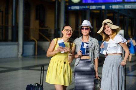 Photo pour Trois jolies jeunes femmes à la gare. Ils ont des passeports et des billets entre leurs mains. Les copines sont heureuses au début d'un voyage passionnant. Temps des vacances d'été . - image libre de droit