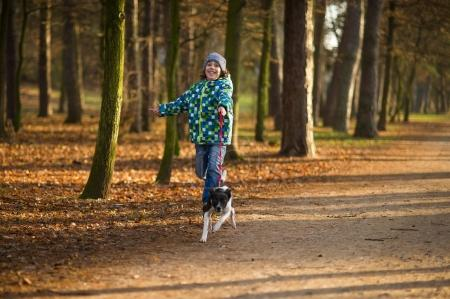 Photo for Boy 10-11 years walking the dog in autumn Park. He is holding the leash of a black-and-white cute dog. - Royalty Free Image
