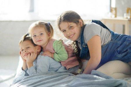 Photo pour Deux sœurs et un frère. Trois enfants de la même famille sont couchés sur le lit. - image libre de droit