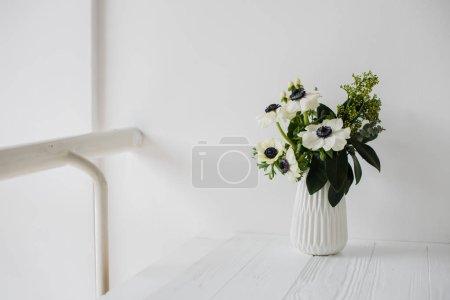 Photo pour Élégant bouquet d'anémones dans un vase sur la table à l'intérieur de la chambre blanche, dcoration maison florale - image libre de droit