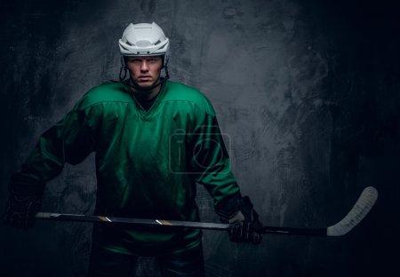 Photo pour Portrait du joueur de hockey en vêtements de protection tient bâton de jeu sur fond gris . - image libre de droit