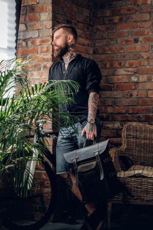 bearded hipster holds leather backpack