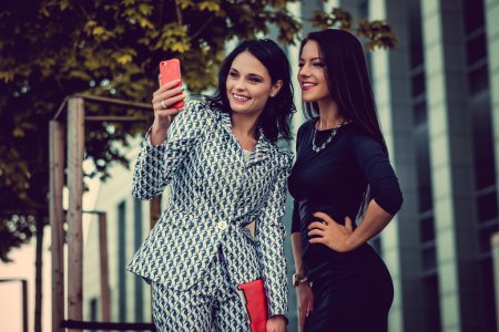 Two fashionable women using smartphone