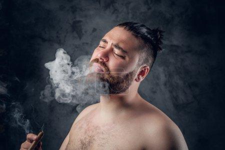 shirtless bearded male smoking cigar