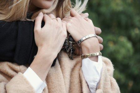 Foto de Cerca del hombre y de mujer brazos con pulseras. - Imagen libre de derechos