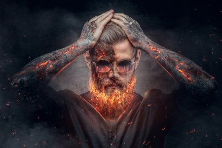 Demonic male with burning beard and arms in fire s...