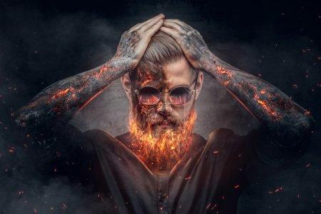 Photo pour Homme démoniaque avec barbe brûlante et bras dans les étincelles de feu . - image libre de droit
