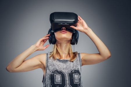 Photo for Young blonde girl wearing virtual reality glasses on grey background. - Royalty Free Image