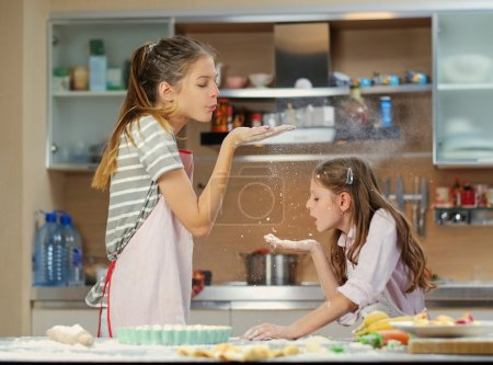 Two girls having fun in the kitchen