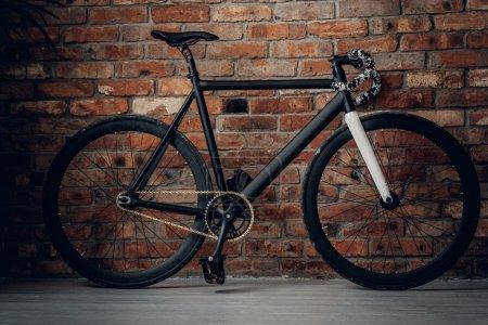 Photo pour Sprint vélo carbone avec un engrenage fixe. Le mur d'un fond de brique . - image libre de droit