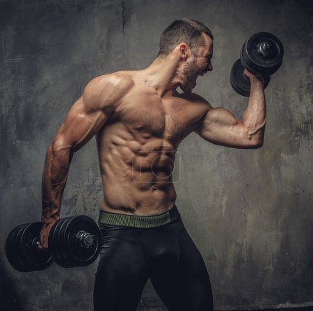 Screaming muscular male with dumbbells