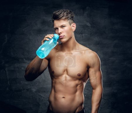 Shirtless muscular male drinking water