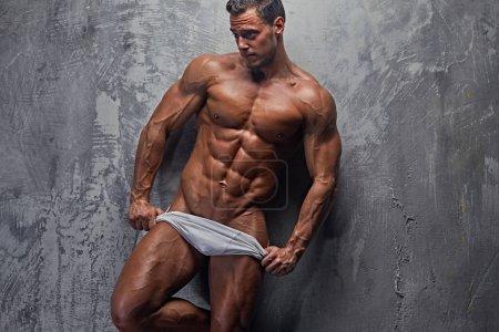 Photo pour Sexy mannequin abdominale en culotte blanche posant dans le fond du mur gris. - image libre de droit