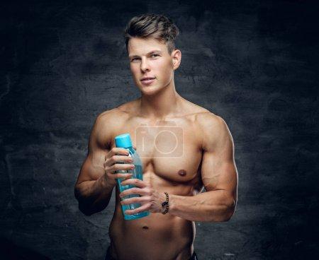 Photo pour L'homme sportif torse nu attrayant tient une bouteille d'eau . - image libre de droit