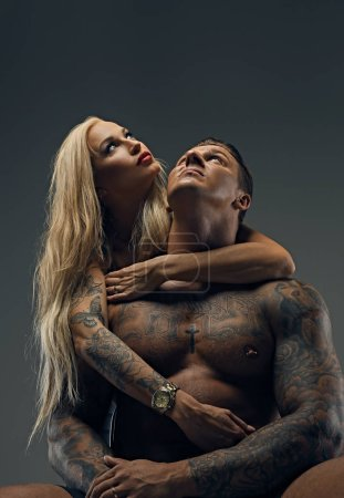 Tattooed man and sexy blonde girl