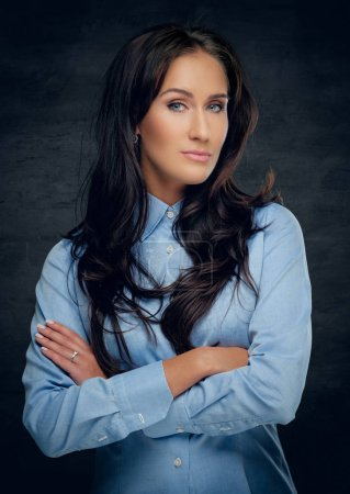 Photo for Studio portrait of brunette woman with crossed arms in a blue shirt on grey background. - Royalty Free Image