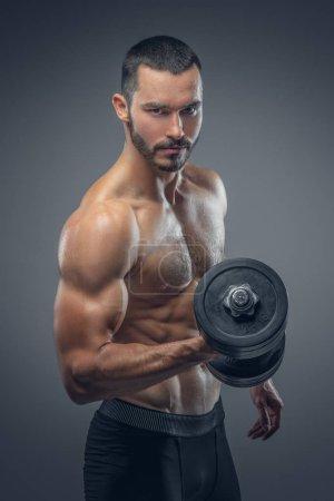 Bearded muscular man holding dumbbells