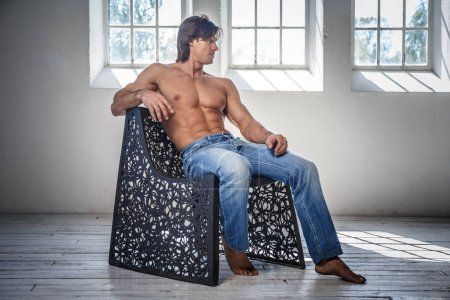 Shirtless man in a jeans sits on a chair
