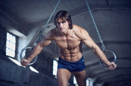 Photo for Athletic muscular man posing with gymnastic rings in a dark industrial tunnel. - Royalty Free Image