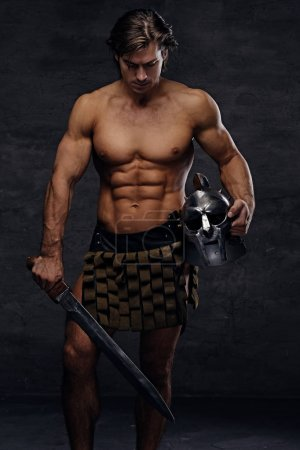 Photo for Portrait of shirtless muscular male in a Rome soldier costume holds silver gladiator helmet and an iron sword in a contrast dramatic studio light. - Royalty Free Image