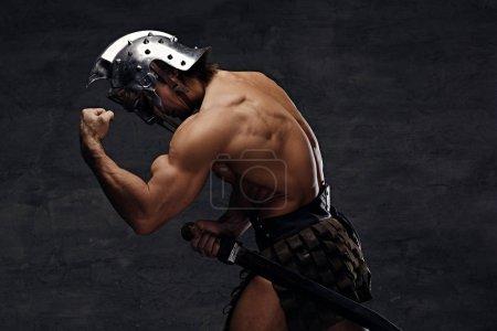 Photo pour Torse nu homme athlétique en casque de gladiateur argent posant sur fond gris. - image libre de droit