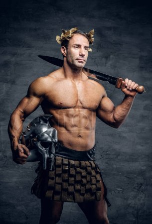 Muscular man holding helmet and sword