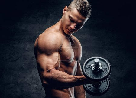 Photo for Athletic shirtless young man fitness model holds the dumbbell with light on dark background. - Royalty Free Image