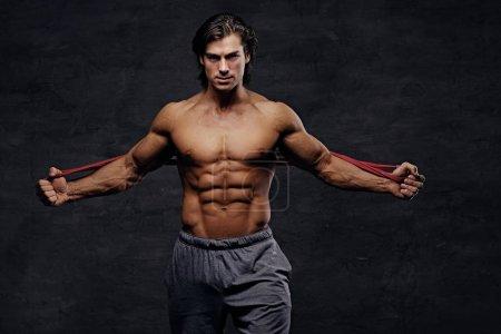 Photo pour Un homme travaille dur avec sangles trx fitness en studio sur fond gris. - image libre de droit